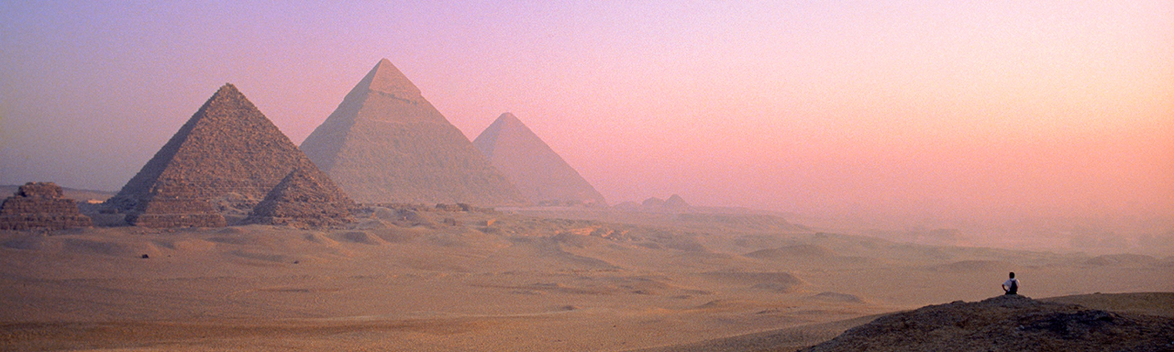 Man sitting on hill looking at Great Pyramids of Giza at sunset
