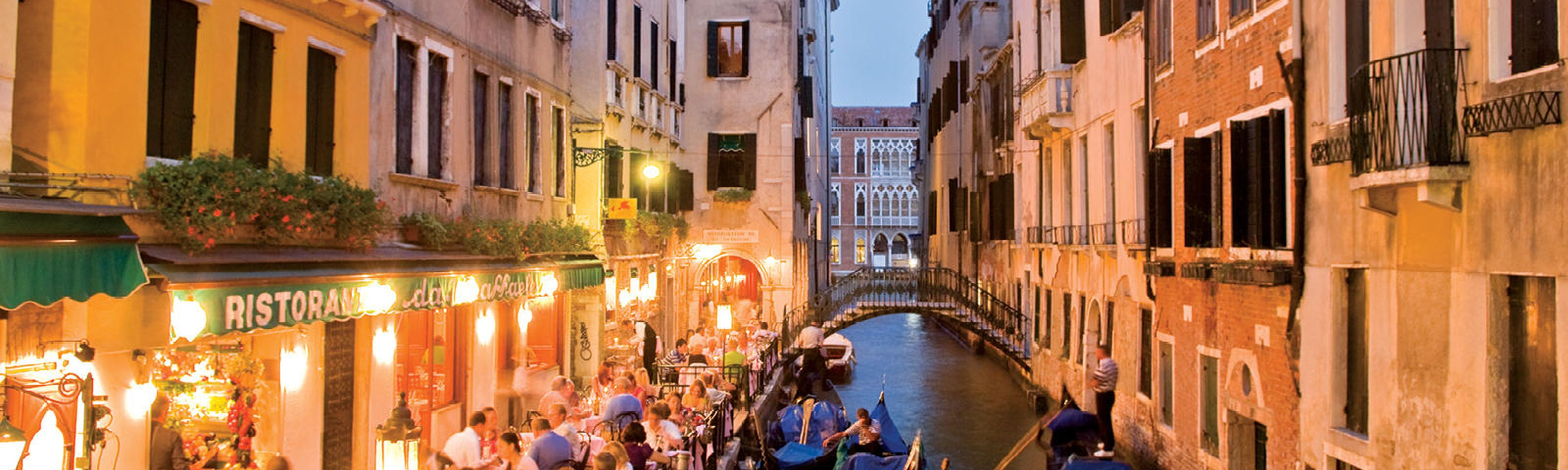 people sitting along a canal at an outdoor cafe in venice at night time