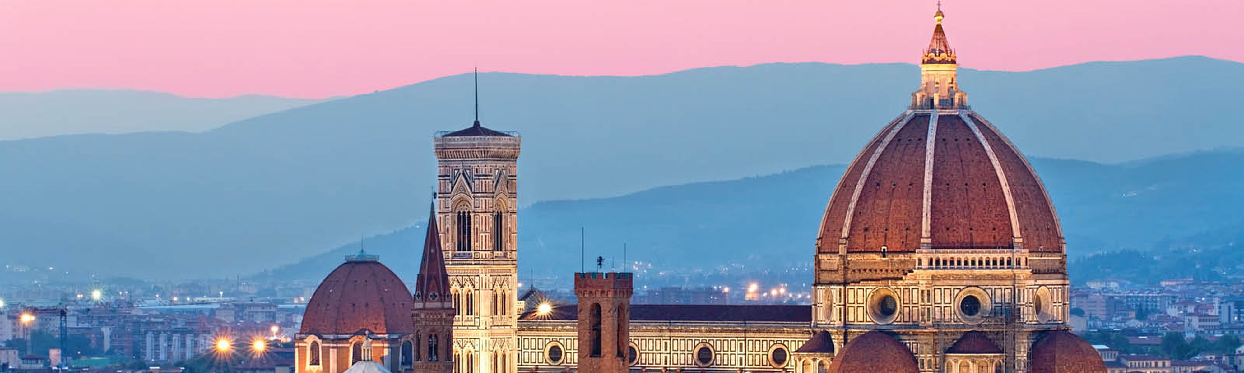 the top of the duomo lit up in florence at sunset