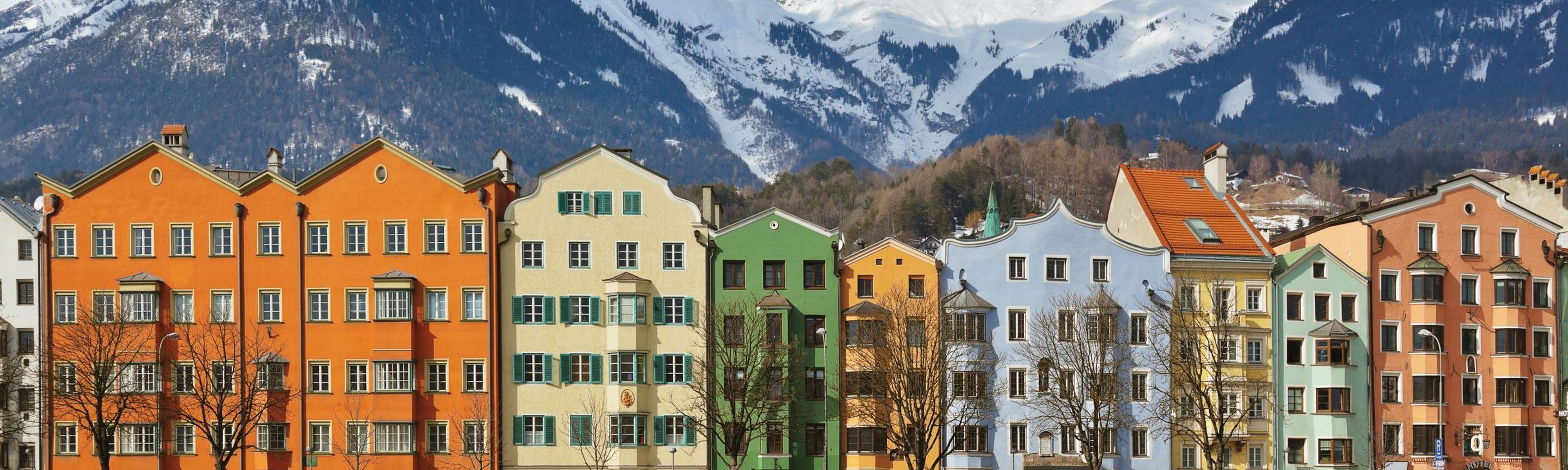 colorful buildings in front of snow capped mountains in innsbruck