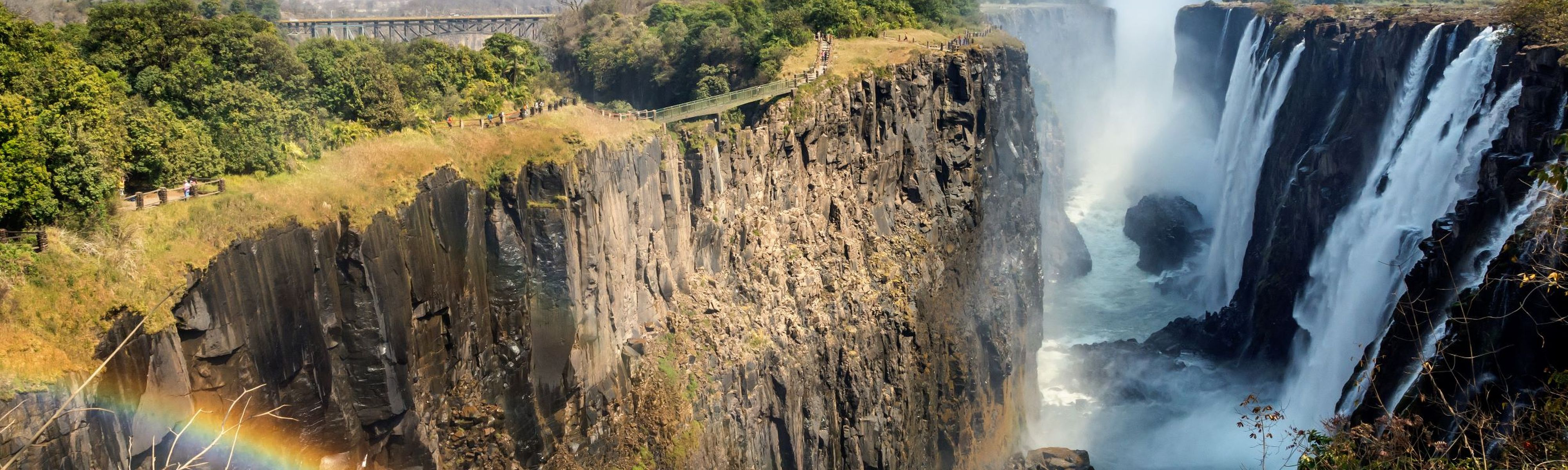 victoria falls with rainbow shining over waterfalls