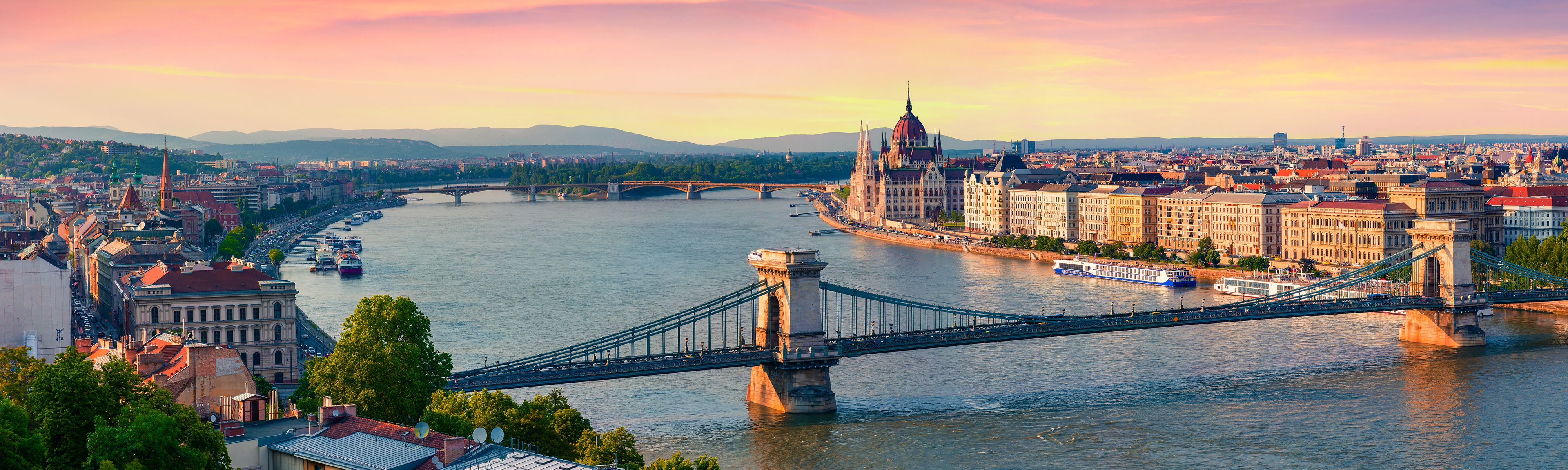 bridge across river with view of the parliament building in budapest at sunset