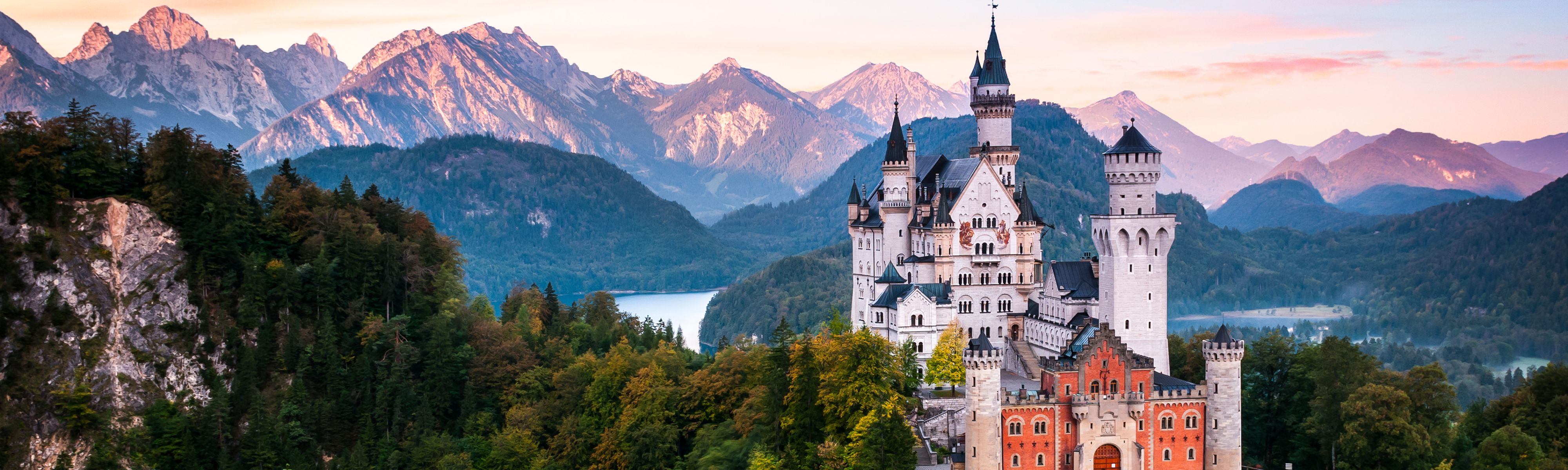 Neuschwanstein Castle at sunrise with panorama of Alps