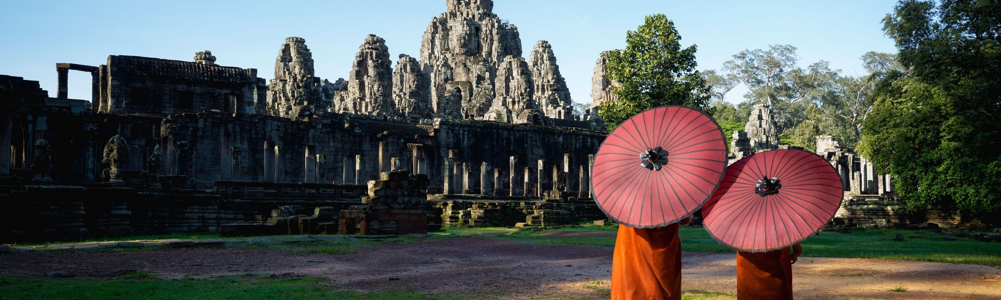 two monks holding red umbrellas walking towards bayon temple