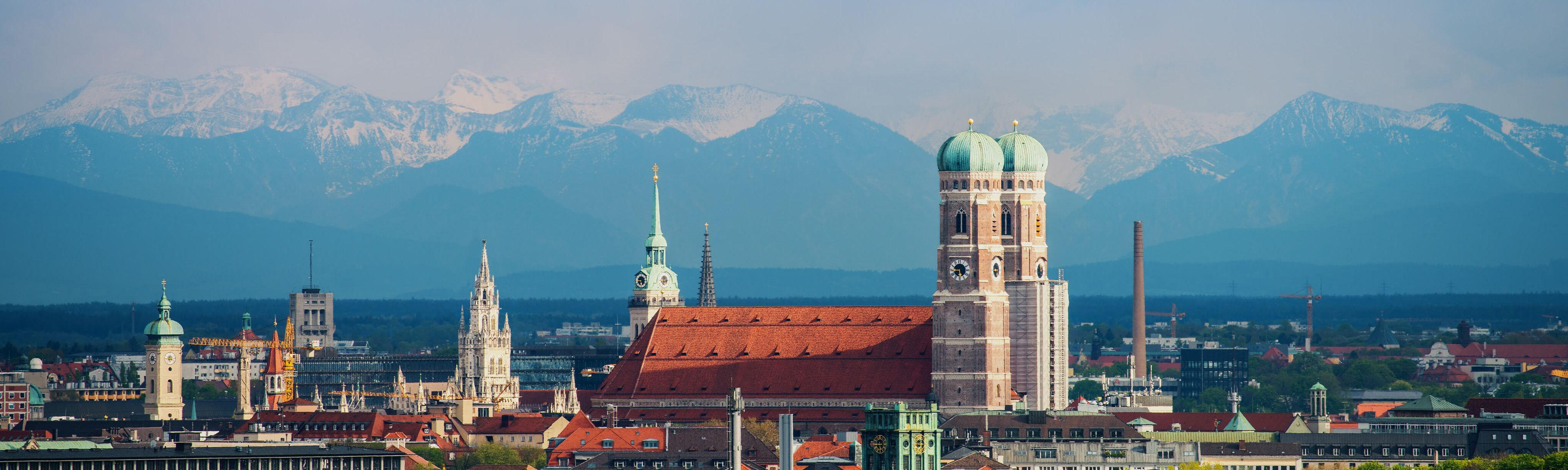 green domed building surrounded by snow capped mountains in munich germany