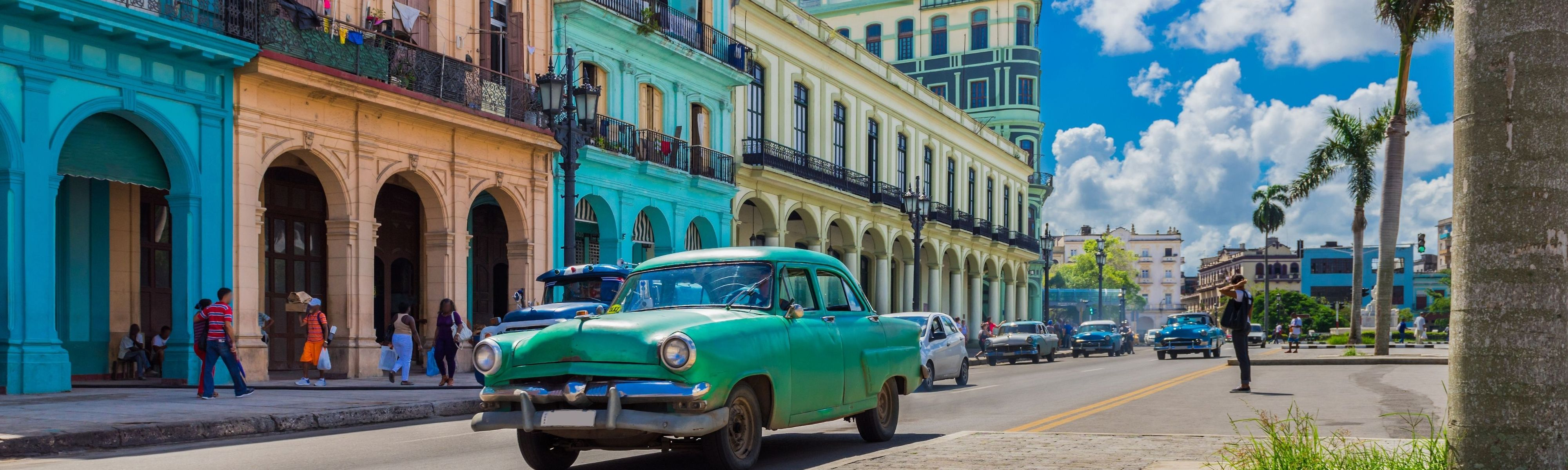 Old cars driving through vibrant Cuba