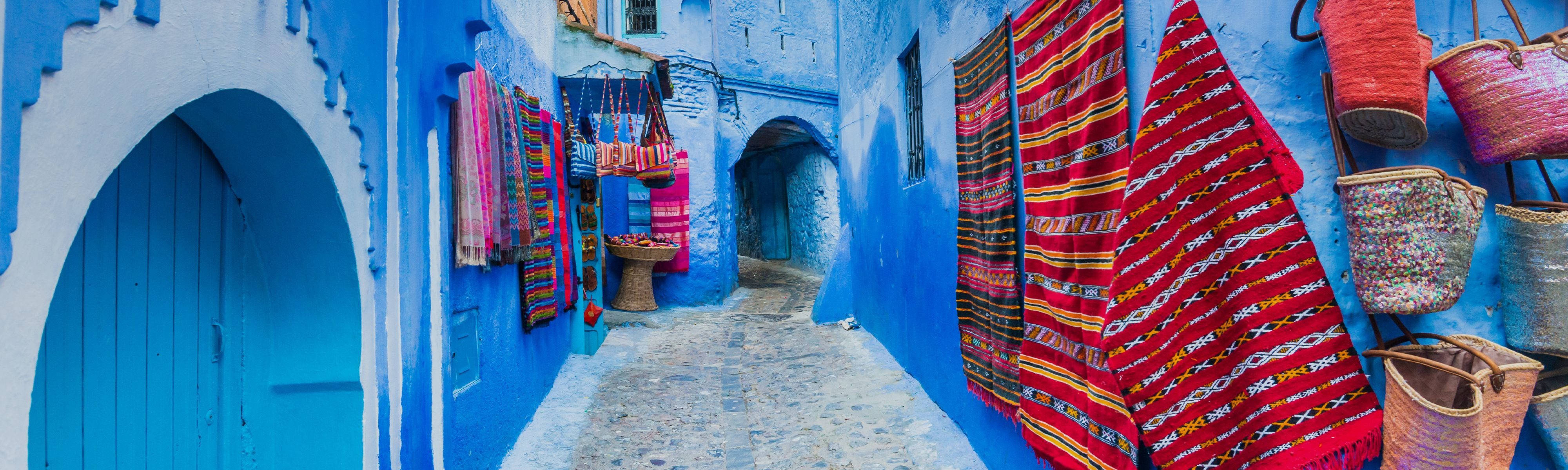 red and white tapestries handing on blue painted building in morocco
