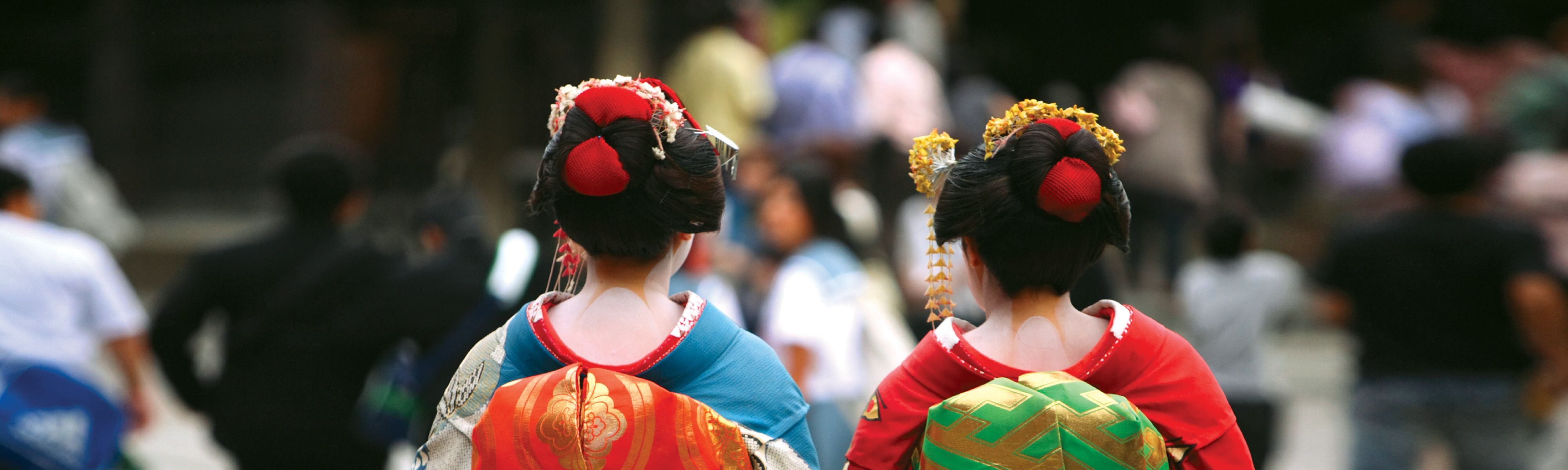 two japanese geisha women dressed in traditional costumes walking away