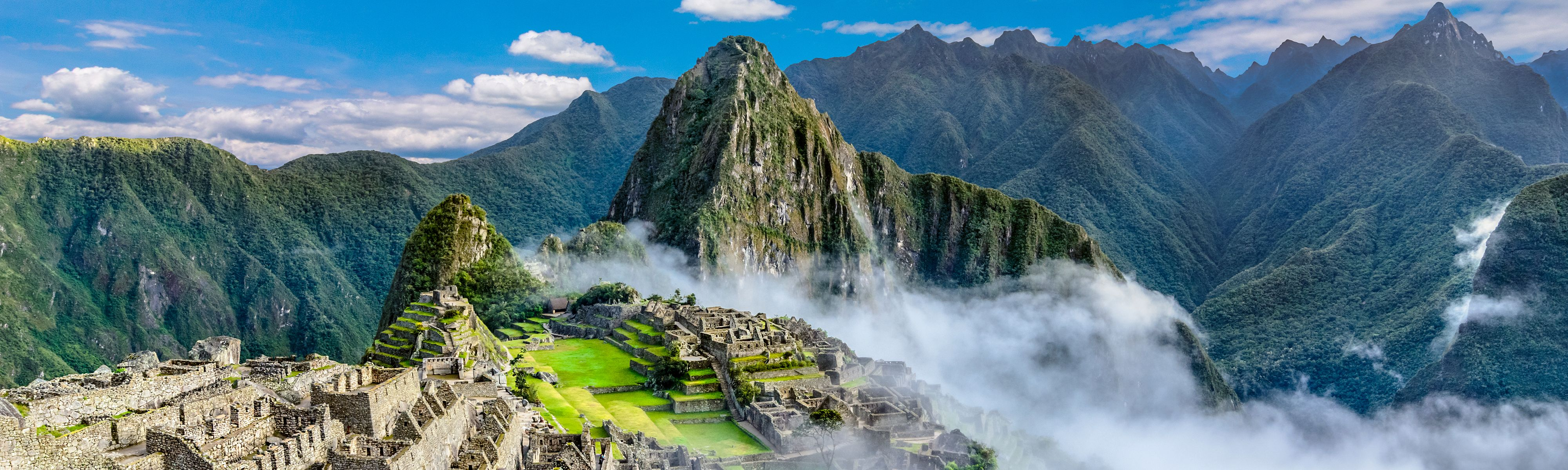 machu picchu with cloud going through mountain range in peru