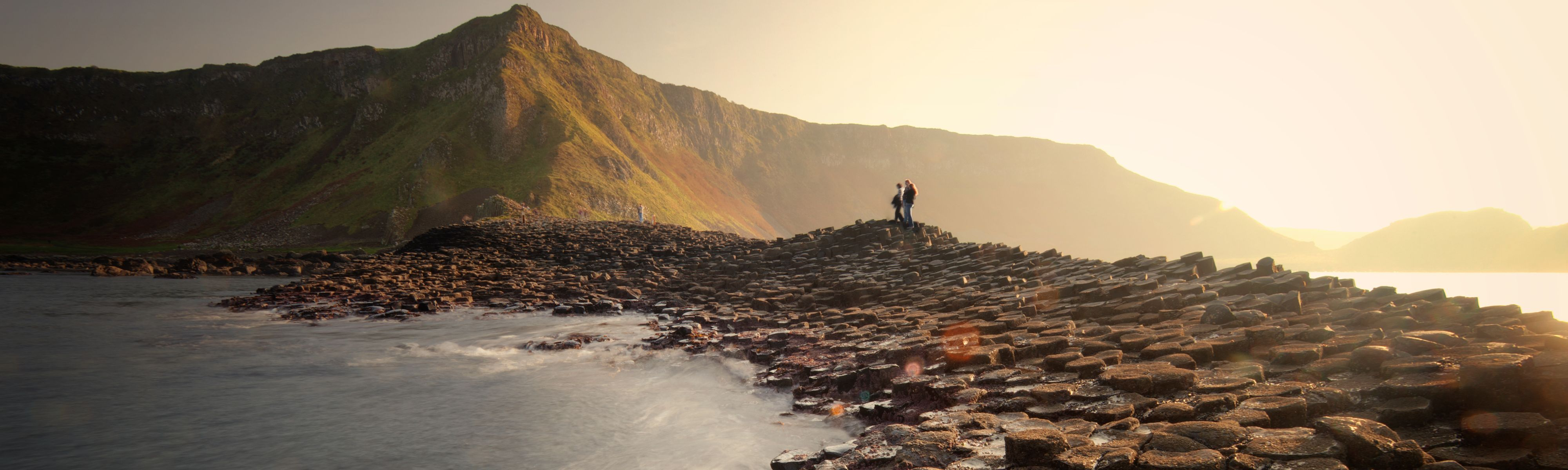 couple walking along stone path along coast in iceland