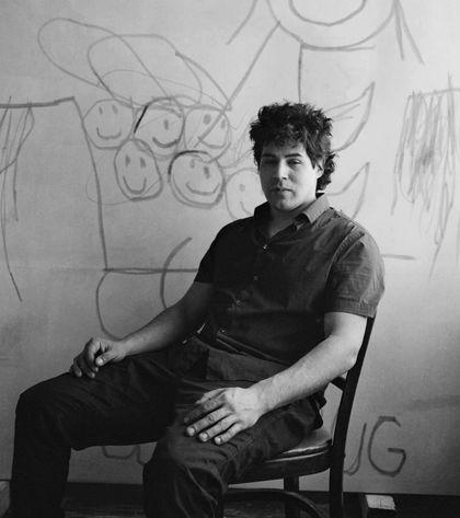 Artist Robert Nava sits on a chair
