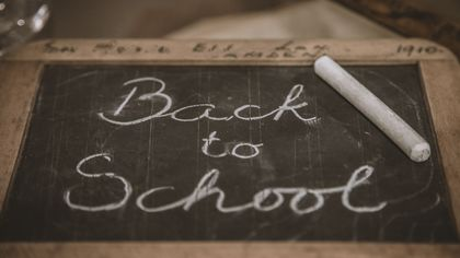 """A picture of a small chalkboard with the words """"Back to School"""" written in a script with white chalk."""