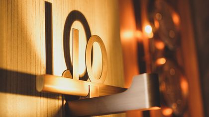 A picture of the number ten as a metal cutout with a light in front of it casting a shadow against the wall behind.
