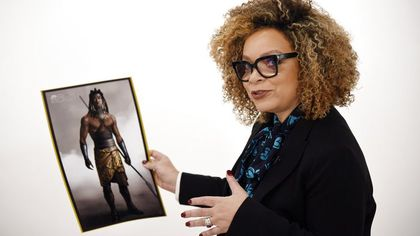 Ruth standing with a picture of a costume design from Black Panther.