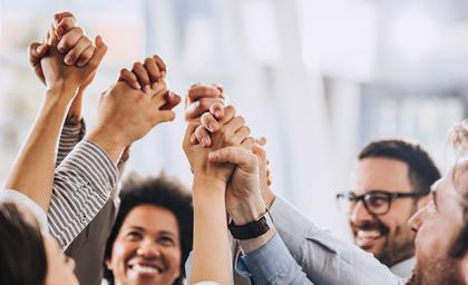 LINK Mobility - Gruppe von Kollegen freut sich über einen gemeinsamen Erfolg und reicht sich die Hände