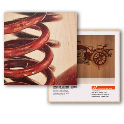 A square tile sample showcasing a red wooden coil. Behind the tile is another square panel, this time showing a glimpse of a motorcycle.