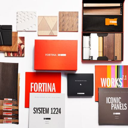 Various samples of material tiles and magazines labelled with products are arranged across a white space.