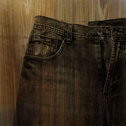A translucent image of jeans is printed in black over a green tinted wood panel.