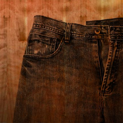 A translucent image of jeans is printed in black over a red tinted wood panel.