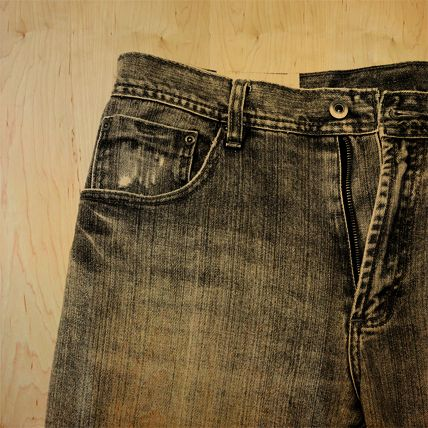 A translucent image of jeans is printed in black over a yellow tinted wood panel.