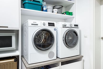 Waschmaschine und Trockner in Waschküche.