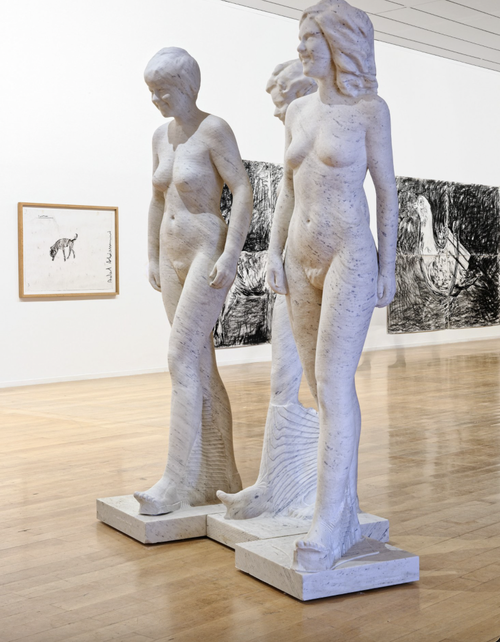 three sculptures of naked women carved from narrow blocks of stone
