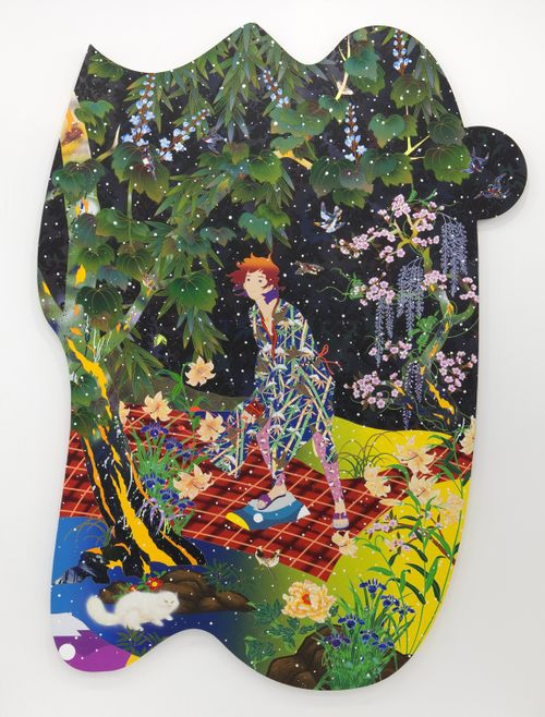 figure dressed in patterned robe stands by a tree surrounded by flowers in bloom and a cat
