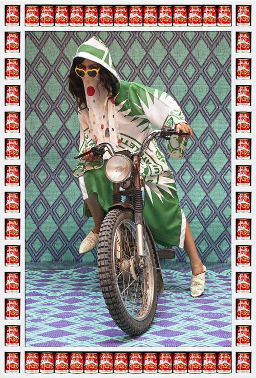 woman in green and white robe with slippers on and heart sunglasses riding a motorbike set against a patterned tapestry backdrop