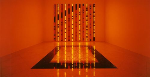 installation view of a room completely bathed in orange light with a plague on the floor and vertical lines of text on the far wall