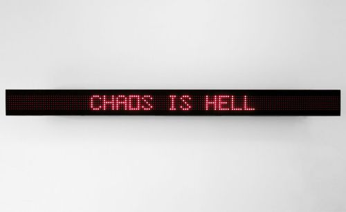 digital red text on a black long, horizontal screen, reading 'CHAOS IS HELL'