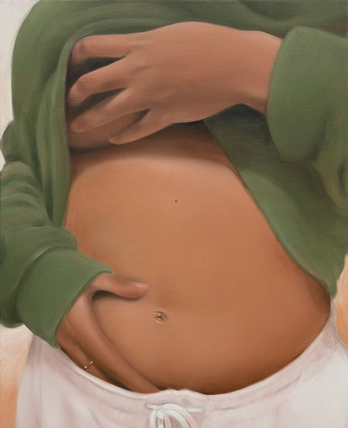 female lifting up her green jumper and placing a hand over her exposed stomach whilst the other clutches her breast