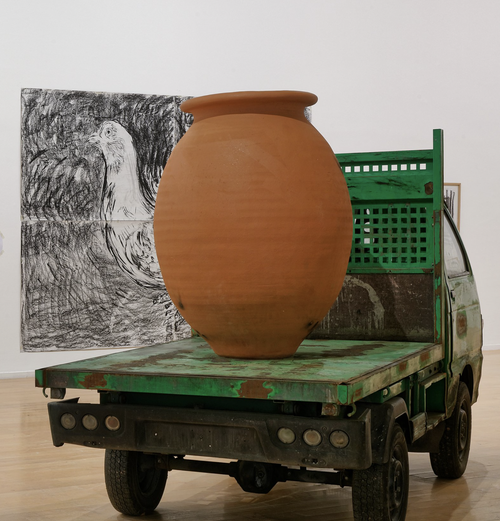 large clay pot on top of a small green pick-up truck in an exhibition space