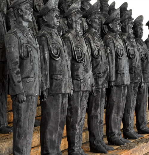 line of sculpted soldiers arranged in rows on wooden platforms