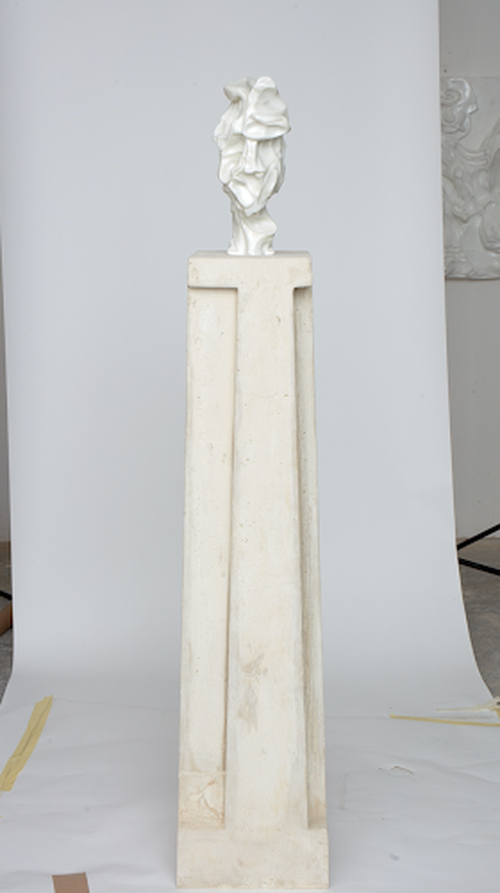 distorted bust of an ambiguous face on a tall marble plinth