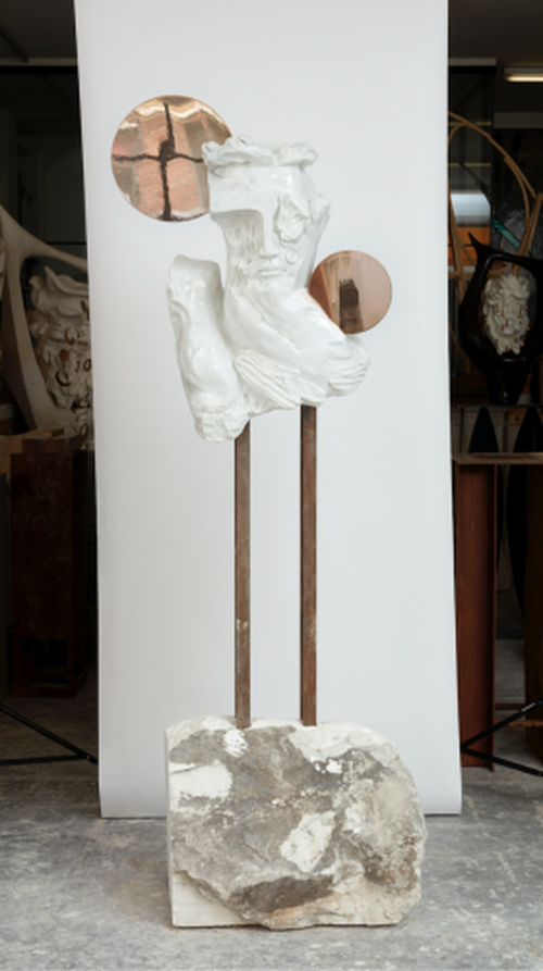 distorted marble bust raised on two metal rods above a block of stone