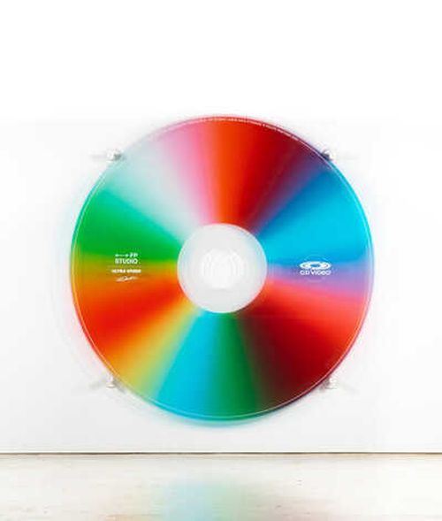 circular CD video disk made up of various bright colours and hung on a white wall