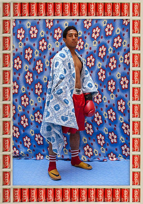Man in slippers and red socks wearing boxing shorts and gloves and stood against a blue floral background