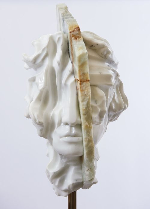 marble bust of a female face with distorted features, placed on a stick