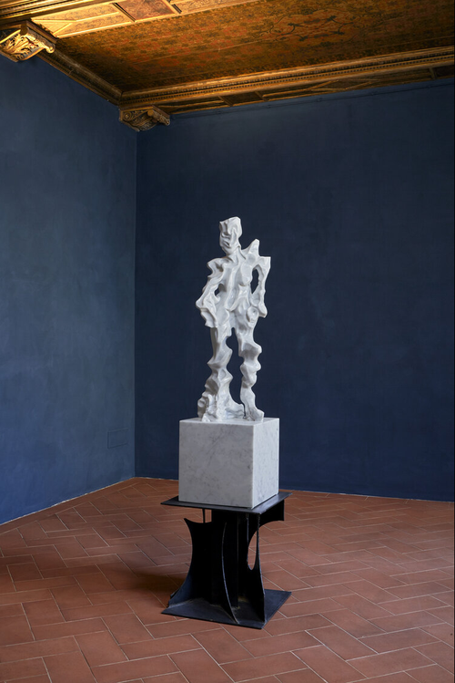 distorted figure emerging from a polished square block of marble which is placed atop a black table in an exhibition space