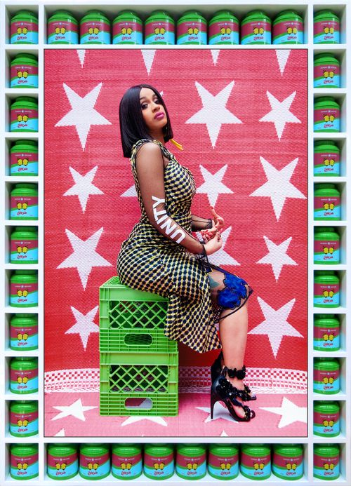 Cardi B wearing heels and with the words 'UNITY' written on her arm, sat on two stacked green crates and set against a backdrop of red and white stars