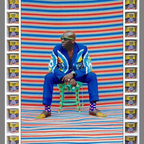 Man in blue tracksuit sat leaning forward on a green stool with sunglasses on and a colourful striped background and floor