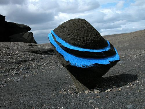 Large black round rock with two bright blue stripes on it and placed in black sand