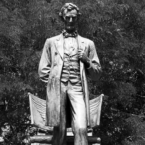 In this celebrated bronze memorial, the figure of President Lincoln stands in a deeply reflective pose before a classically styled chair, from which he appears to have just risen. With his left hand on the lapel of his meticulously rendered period clothing, Lincoln looks slightly downward and steps forward, his left foot just breaking the edge of the plinth on which he stands.