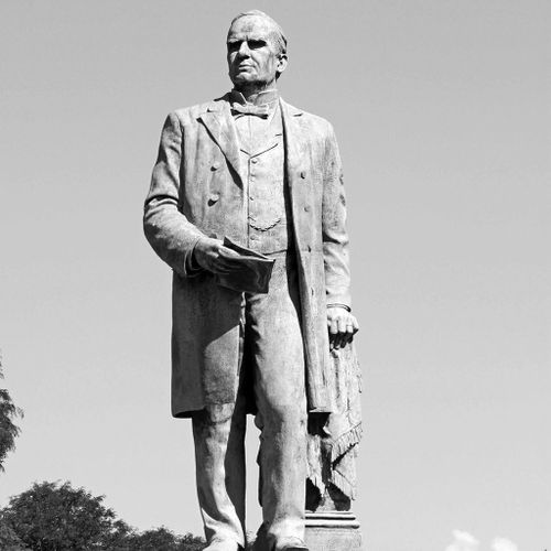 The Mckinley Monument presents an image of the president with his left hand supported on a draped pedestal that stands slightly behind his body, and his right holding a sheaf of papers or folio. Dressed in formal, late 19th-century attire, he looks into the distance in the direction of his right shoulder.