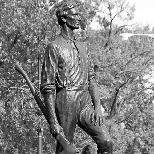 Lincoln, Rail Splitter show the Lincoln as a young man in humble work clothes. Looking resolutely holding an axe at his side in his right hand, his left hand resting on his right leg, which is bent from standing on slightly raised terrain.