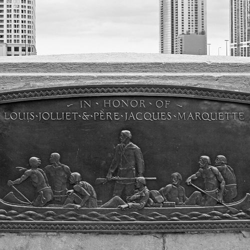 These oblong, shallowly carved tablets, mounted to the inner parapet walls of DuSable Bridge show in figures of French explorers and their American Indian guides rowing and disembarking from their canoes. In both tablets, the figures move as if in concert, in front of an ideal space with no indication of place, but rather against a blank background.