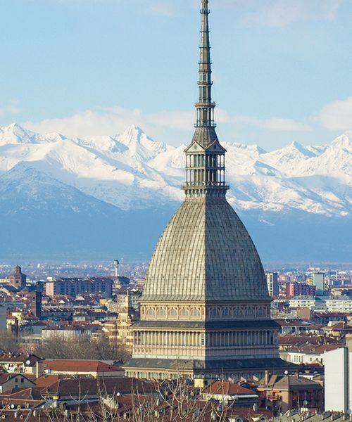 mole antoneliana building in turin italy with alps in background