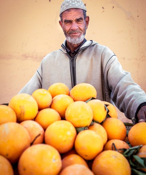 a man selling oranges at a stand in morocco