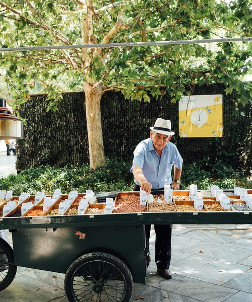 a street vendor selling nuts from his cart on a sunny day