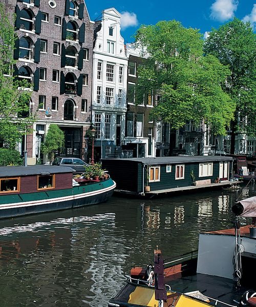 canal boats docked in amstel river in amsterdam